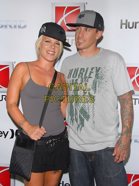 PINK & CAREY HART.The Saturn X Games Kick Off Party introducing the new Saturn VUE Green Line Hybrid held at a special temporary space created for the event in Hollywood , California, USA..August 2nd, 2006.Ref: DVS.half length jeans denim tattoos pinnk black bag skirt grey gray tank top baseball cap hat couple married bag.www.capitalpictures.com.sales@capitalpictures.com.©Debbie VanStory/Capital Pictures