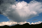 Thunderhead cloud forms in a blue sky over mountains in New Mexico.