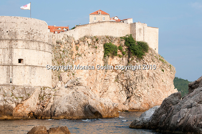 Looking up at the city wall of Dubrovnik, Croatia at sunset with Fort Bokar and huge rocks in the foreground.