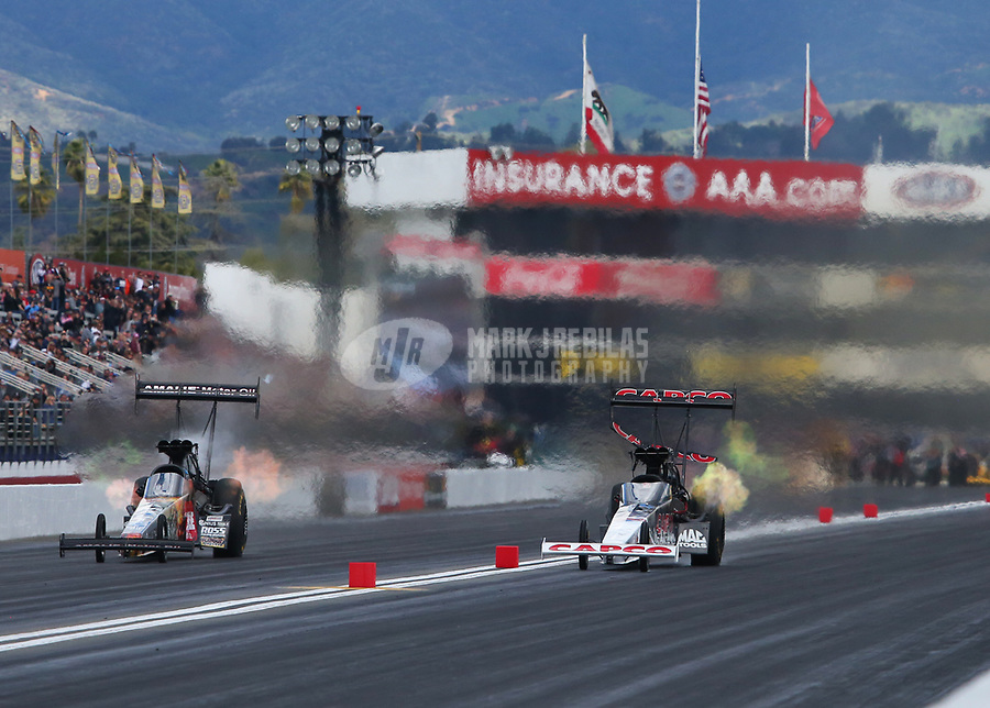 Feb 9, 2019; Pomona, CA, USA; NHRA top fuel driver Billy Torrence (right) loses a rear wing element as he races alongside Terry McMillen during qualifying for the Winternationals at Auto Club Raceway at Pomona. Mandatory Credit: Mark J. Rebilas-USA TODAY Sports