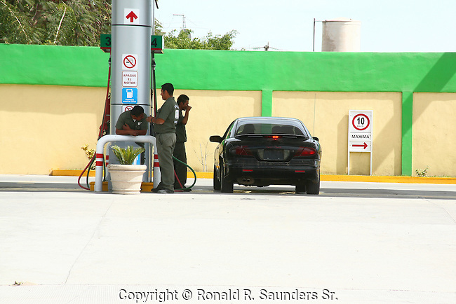 Car pulls in to gas station. Attendant prepares to fill gas.<br />