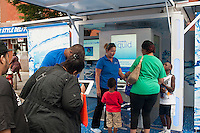 """JPMorgan Chase promotes its refillable debit card, """"Liquid"""" at the Harlem Week street fair on West 135th Street in Harlem in New York on Sunday, August 19, 2012. (© Richard B. Levine)"""
