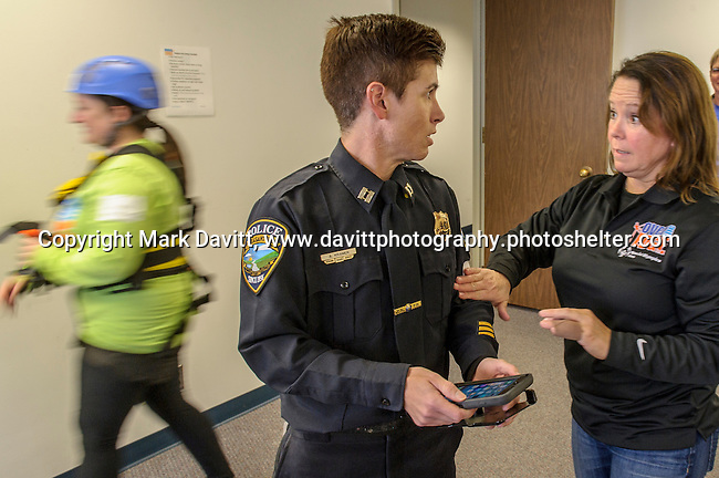 "Pleasant Hill Police Captain Amy Kramer talks with Michelle Leonard, Dallas Center Police before getting fitted with a harness to go ""Over the Edge"" of the 345-ft. Financial Center in Des Moines in support of Special Olympics Iowa Oct. 26. Leonard raised $1,000 to support  the cause but was not able to go because of a hand injury."
