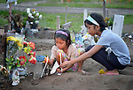 Two girls light candles at the grave of a friend buried in a church yard in the city of Palo, in the Philippines province of Leyte, where typhoon Haiyan killed hundreds of people in November 2013. The storm was known locally as Yolanda.