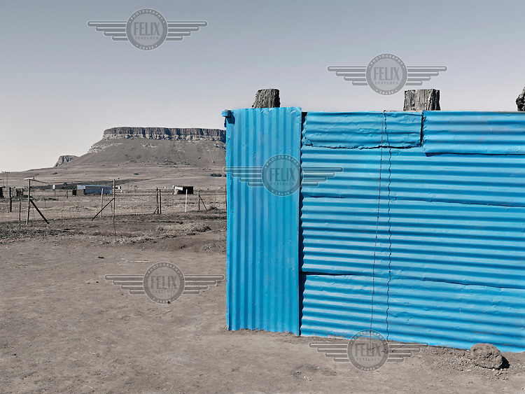A neatly painted blue corrugated iron shack.  Graeme Williams' pictures of the environments occupied by some of South Africa's poorest people focus on the interiors and exteriors of people's homes, accentuating the minutiae of the occupants' day-to-day dwelling places. The bright colours captured in these photographs are suggestive of resilience, hope and a sense of humanity that survives in these poverty-stricken communities...