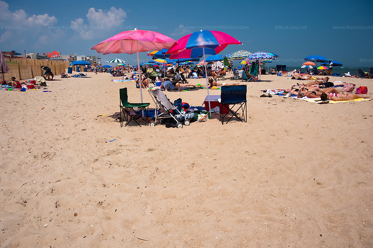 A family's territory stands temporarily abandoned at lunch time on a summer beach day at Rehoboth Beach, Delaware, USA.