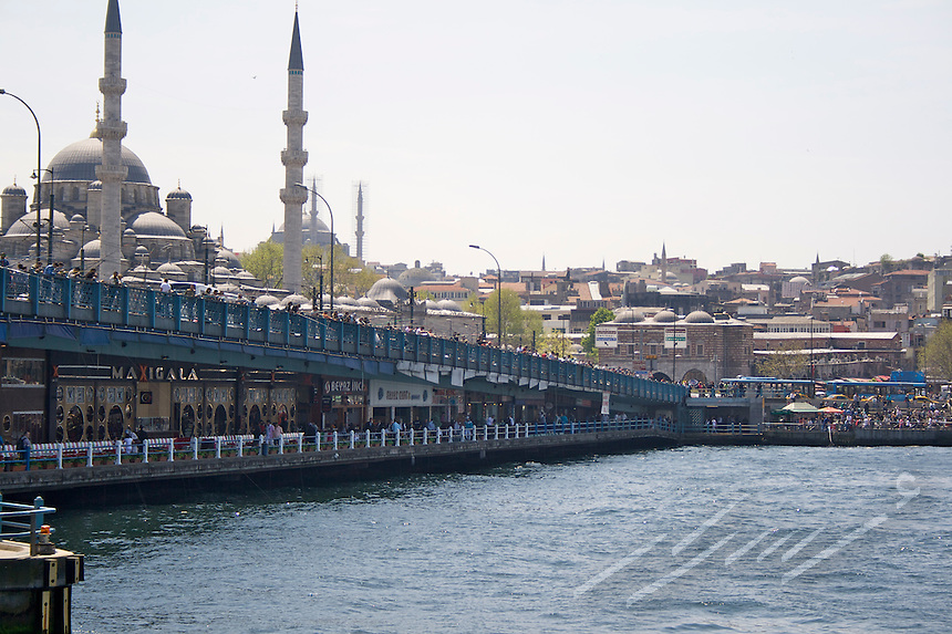 The typical atmosphere of Istanbul city, Turkey.  Bosporus waters crossed by a wide bridge were restaurants, shops, people and vehicles.  Urban suburbs on the back with minarets and domes of mosques.