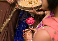 A girl holds a flower in her henna-decorated hands during the wedding ceremony between Suketu Soni and Divya Agarwal in Navsari, Gujarat, India, Jan. 3, 2008. Traditionally, Indian weddings last days longer than their American counterparts.