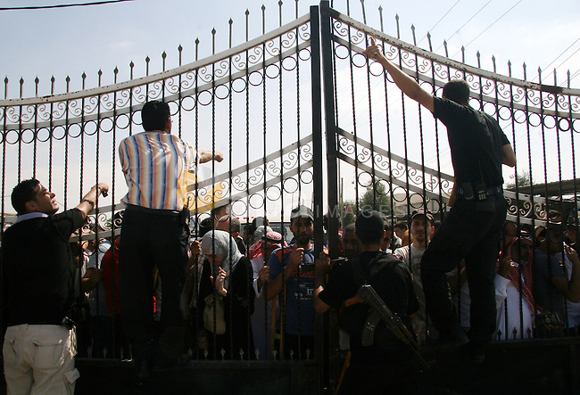 Palestinians wait at the gate of the Rafah border crossing to Egypt on July 1, 2008 in the southern Gaza Strip. Egypt opened the border crossing with Rafah on Tuesday for three days for the limited passage of people such as Palestinians stranded in Egypt and Gazans seeking medical treatment abroad.