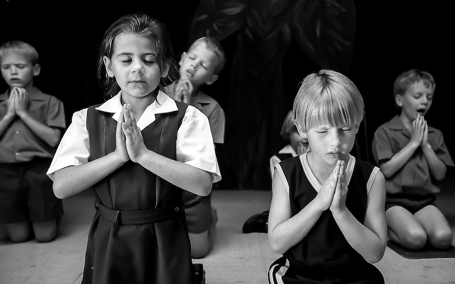 Ursula Nieuwoudt (front lefft) prays with her classmates at her primarily white school in the Hennops River area just outside of Johannesburg, South Africa.  Ursula, an Afrikaner (South African of Dutch descent) lives with her parents and two sisters on a farm (not in operation).  Her father, Kobus, is a town planner and consultant and her mother, Annelie, owns a topiary.