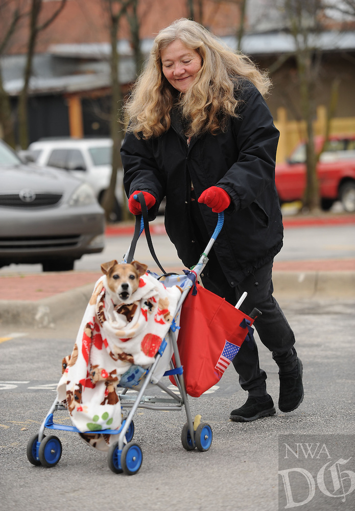 NWA Media/ANDY SHUPE - Carol Ackley of Fayetteville smiles Sunday, Dec. 28, 2014, as she walks with her dog, Lucy, in a baby stroller off Dickson Street in Fayetteville. Lucy is 13 and because of her age enjoys being shuttled in the stroller though, according to Ackley, she will jump out if she sees a squirrel.