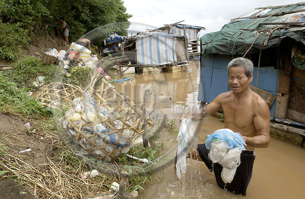 Hanoi-Vietnam, Ha Noi - Viet Nam - 24 July 2005---A group of internal (illegal) migrants / displaced homeless people live on the banks of the Red River in floating huts under miserable conditions, earning little money from begging and waste recycling; here, a man washing plastic waste to be sold for recycling---housing, people, poverty, labour---Photo: Horst Wagner/eup-images