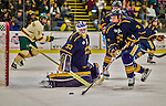 29 December 2013:  Canisius College Golden Griffins goaltender Keegan Asmundson, a Junior from Inver Grove Heights, MN, makes a second period save as teammate Doug Jessey, a Junior from Langdon, Alberta, clears the rebound during play against the University of Vermont Catamounts at Gutterson Fieldhouse in Burlington, Vermont. The Catamounts defeated the Golden Griffins 6-2 in the 2013 Sheraton/TD Bank Catamount Cup NCAA Hockey Tournament. Mandatory Credit: Ed Wolfstein Photo *** RAW (NEF) Image File Available ***