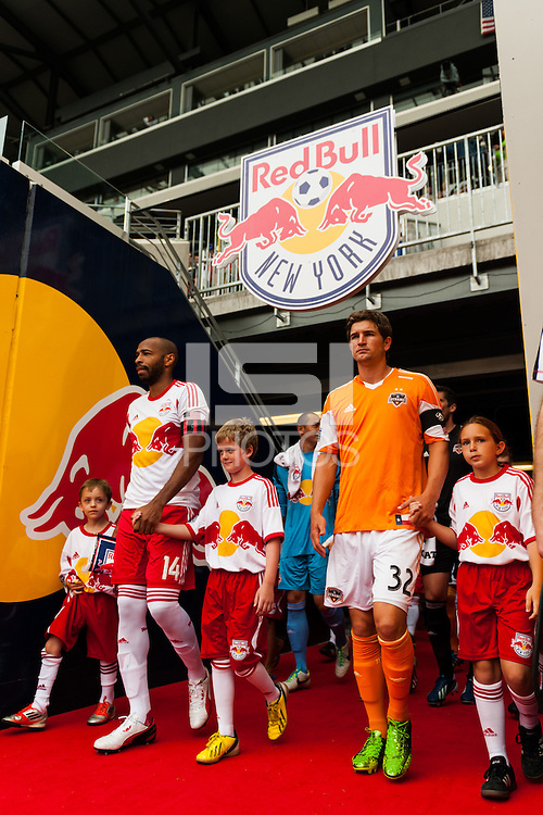 Thierry Henry (14) of the New York Red Bulls and Bobby Boswell (32) of the Houston Dynamo lead their teams out of the tunnel. The New York Red Bulls defeated the Houston Dynamo 2-0 during a Major League Soccer (MLS) match at Red Bull Arena in Harrison, NJ, on June 30, 2013.