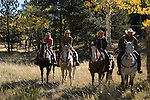 Family group outdoors on a crisp and cool fall morning riding horses in Rocky Mountain National Park, near Estes Park, Colorado, USA