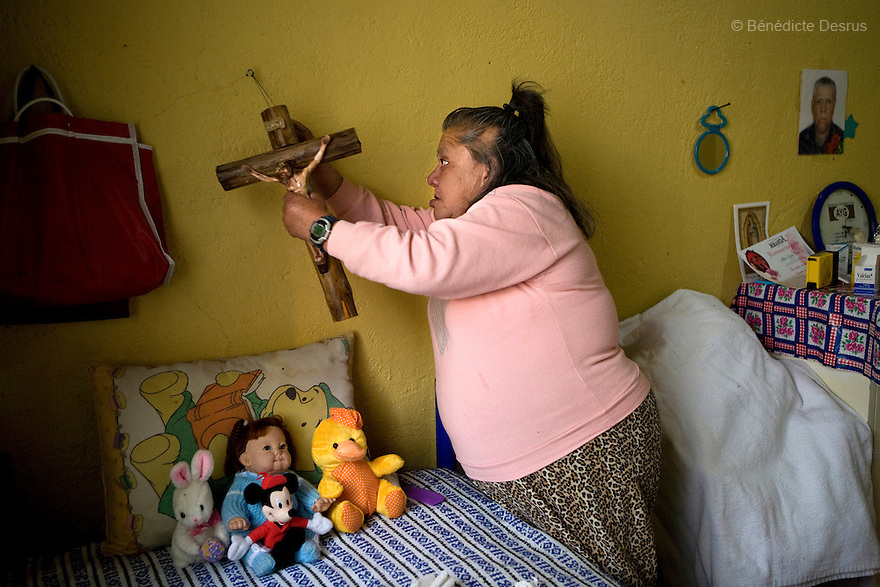 Canela, a resident of Casa Xochiquetzal, adjusts the cross she keeps above her bed at the shelter in Mexico City, Mexico on December 11, 2008. Casa Xochiquetzal is a shelter for elderly sex workers in Mexico City. It gives the women refuge, food, health services, a space to learn about their human rights and courses to help them rediscover their self-confidence and deal with traumatic aspects of their lives. Casa Xochiquetzal provides a space to age with dignity for a group of vulnerable women who are often invisible to society at large. It is the only such shelter existing in Latin America. Photo by Bénédicte Desrus
