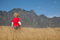 Young child walking through long gras with the peaks of the Remarkables Mountains in background, Queenstown, South Island, New Zealand