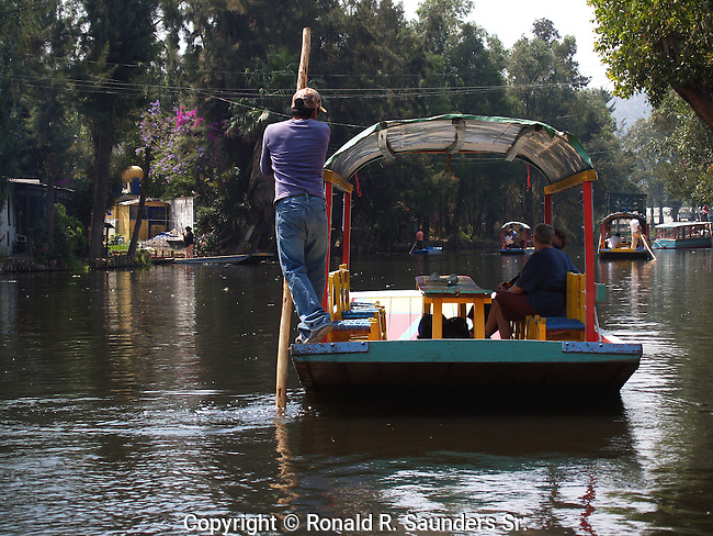 """[UNESCO WORLD HERITAGE SITE] (4)<br /> <br /> BOATSMAN STEERS PASSENGERS ALONG LAKE XOCHIMILCO and the FLOATING GARDENS<br /> <br /> Xochimilco is one of the sixteen boroughs within Mexican Federal District. Today,the borough consists of eighteen neighborhoods along with fourteen villages that surround it. While the neighbhoods are somewhat in the geographic center of the Federal District, it is considered to be """"south"""" and has an identity separate from the historic center of Mexico City. Xochimilco is best known for its canals, which are left from what was an extensive lake and canal system that connected most of the settlements of the Valley of Mexico. These canals, along with artificial islands called chinampas, attract tourists and other city residents to ride on colorful gondolas called<br /> """"trajineras"""". Its Hispanic past, has made Xochimilco a World Heritage Site."""