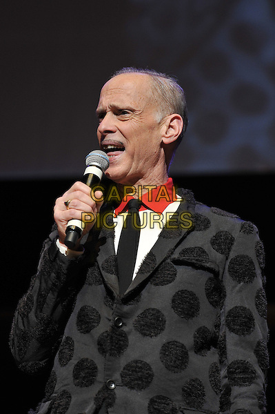 John Waters performing his one man show, 'A John Waters Christmas', Royal Festival Hall, London, England. .5th December 2011.stage concert live gig performance profile black polka dot jacket microphone half length mouth open .CAP/MAR.© Martin Harris/Capital Pictures.