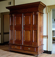 A massive antique oak wardrobe stands in the hallway