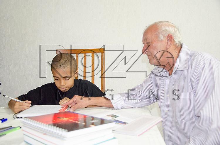 Avô ajudando na lição de caso do neto, São Paulo - SP, 02/2013.