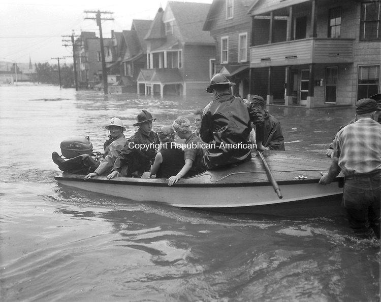 Members of the Mahoney family are ferried from their Waterbury home at the corner of North Riverside and West Main Streets up West Side Hill by volunteer firemen.