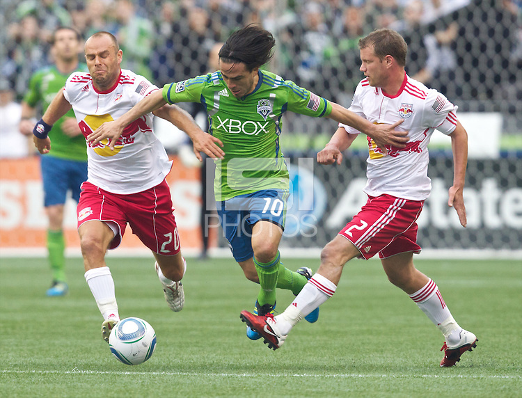 Seattle Sounders FC midfielder Mauro Rosales splits Seattle Sounders FC midfielders Joel Lindpere and Teemu Tainio during play at Qwest Field in Seattle Saturday June 23, 2011. The Sounders won the game 4-2.