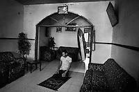 19 year old Ali Ayrhim kneels down to pray at home before he goes surfing. His surf board is propped up against the wall behind him.