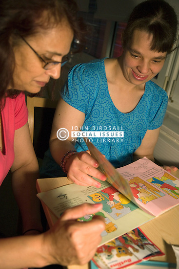 Day Service Support worker looking at a story book with service user with learning disability
