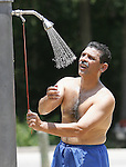 6/13/06--Miguel Hernandez of Sugarland pulls the cord and waits for the water to cool him off at an outdoor shower that is set up along the jogging track in Memorial Park. Hernandez was running the track, which is approximately 3 miles long, for exercise.  Steve Campbell, Chronicle Staff