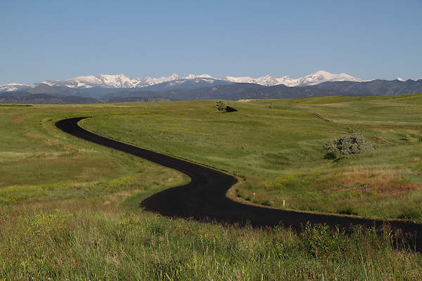 Winding paved road in the foothills with the Indian Peaks Wilderness Area behind, Boulder, Colorado, USA