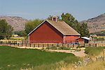 Red barn with single cupola in rural central Oregon