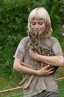 Rehkitz, Reh-Kitz, Kind hat wenige Tage altes, verwaistes Jungtier auf dem Arm, Kitz, Tierkind, Tierbaby, Tierbabies, Europäisches Reh, Ricke, Weibchen, Capreolus capreolus, Roe Deer, Chevreuil