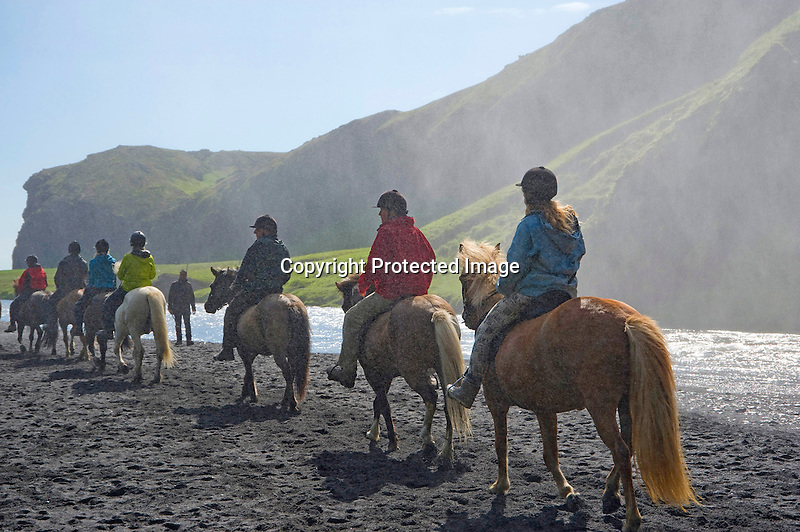 Horseback Riders Being Showered by Mists from Skogafoss Waterfall in South Iceland
