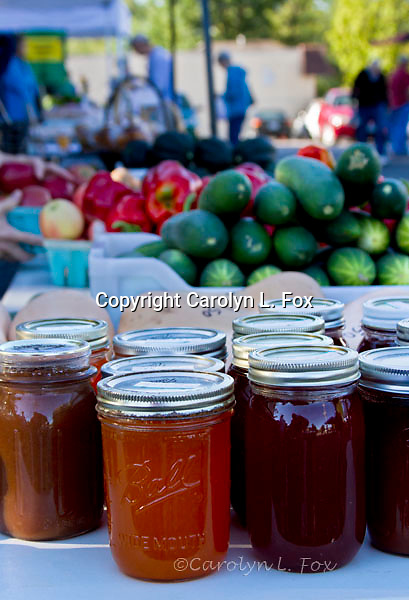 Vegetables, fruit and preserves sit on a table at a local farmers' market.
