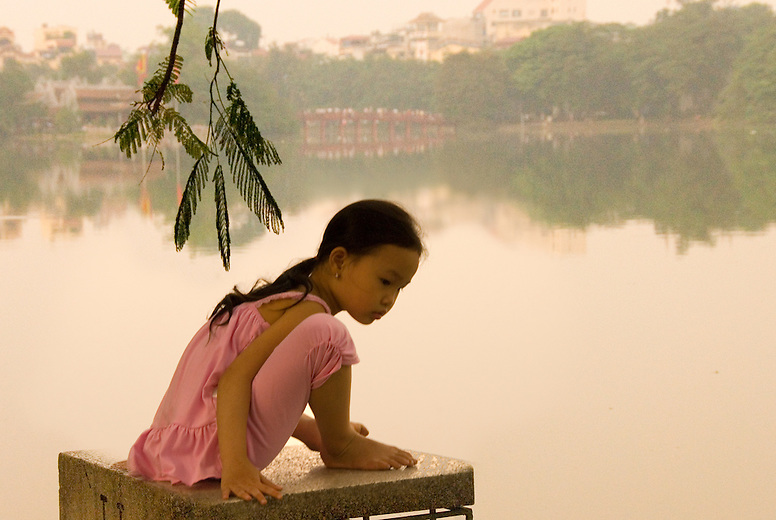 A young girl sits by Hoan Kiem Lake in Hanoi, Vietnam