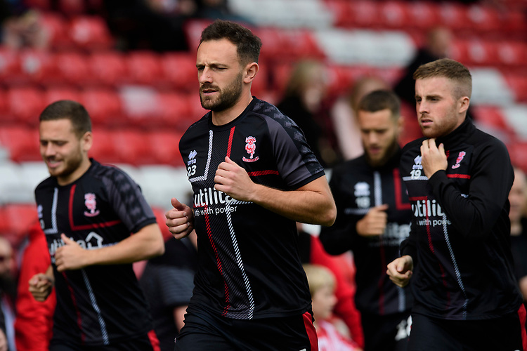 Lincoln City players, from left, Jack Payne, Neal Eardley and Joe Morrell during the pre-match warm-up<br /> <br /> Photographer Chris Vaughan/CameraSport<br /> <br /> The EFL Sky Bet League One - Lincoln City v Sunderland - Saturday 5th October 2019 - Sincil Bank - Lincoln<br /> <br /> World Copyright © 2019 CameraSport. All rights reserved. 43 Linden Ave. Countesthorpe. Leicester. England. LE8 5PG - Tel: +44 (0) 116 277 4147 - admin@camerasport.com - www.camerasport.com