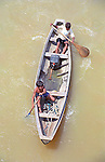 Boys paddle a canoe on the Amazon River in Brazil