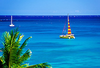 A catamaran takes tourists on excursions  to experience the beauty of Hawaii's blue waters and warm trade winds. Sailing tours originate on waikiki beach.