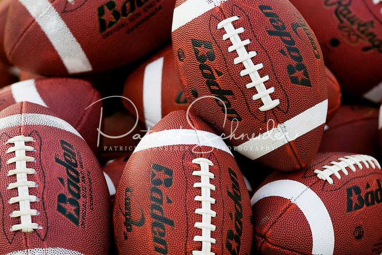 Tight shot of Baden footballs in a pile (pile of footballs). For several weeks each summer, the Offense-Defense Football Camp gives children between the ages of seven and 18 a chance to participate in full-contact football practice. Young football enthusiasts learn football theory and hands-on football practice under the guidance of NFL coaches, NFL players and college coaches who teach at the camps. Offense-Defense football summer camps are offered in several dozen locations across the U.S. Photos in this summer youth football camp were taken at the Charlotte, NC, camp, held at the University of North Carolina Charlotte (UNCC) from July 19-23, 2009.