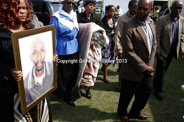 HAMMARSDALE - 14 September 2013 - Family of Paulos Boy Maritlane (seen in framed photo) arrive at the service in the Mpumulanga Sports ground ahead of his burial. Maritlane was one of 22 people killed a week earlier when a runaway lorry crashed into four minibus taxis and two cars. Picture: Allied Picture Press/APP