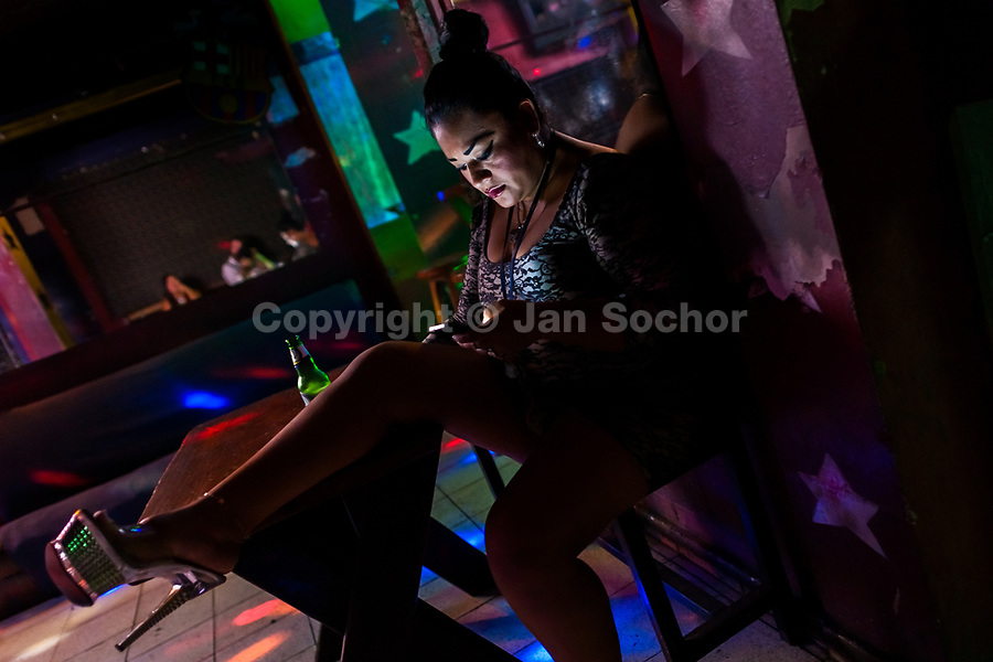 A Salvadoran sex worker looks at the phone screen while waiting for customers in a sex club in San Salvador, El Salvador, 9 April 2018. Sex workers' task in the club is to be an entertaining and seductive companion. Performing erotic dance on the pole they make the customers stay as long as possible and buy relatively expensive alcoholic beverages from which they have a certain share. Sex workers are not obliged to have sexual intercourse with the club customers, they decide themselves, usually according to their current economic situation.