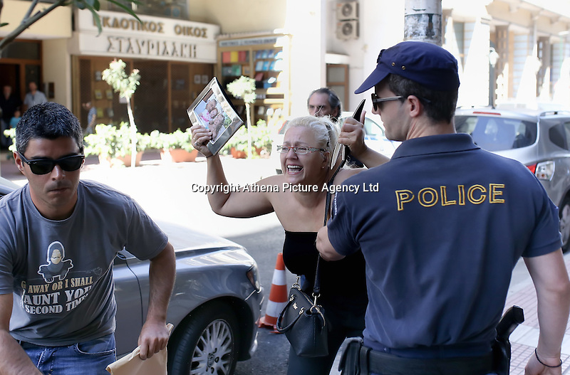 Pictured: A relative of two of the victims, Theodosios Katifes and five year old Sevasti Katife is restrained by police as Tharsivoulos Lykourezos, the captain of the speedboat arrives at Piraeus Court.<br /> Re: Tharsivoulos Lykourezos, the captain of a speedboat that collided with a tourist boat off the Greek island of Aegina, leaving four people dead, has appeared in court and was given until Friday to prepare his defense.<br /> Relatives of the victims shouted insults and were held back by police as the 77-year-old arrived at the courthouse in Greece's main port city of Piraeus.<br /> The speedboat called Duente collided Tuesday with a tourist boat called Antonia carrying more than 20 people from the island to a beach on a nearby islet. The dead included a 5-year-old girl and her father. Authorities initially said the child was about 9.<br /> The health ministry says 16 people in all were hurt, with five requiring hospital treatment. Two suffered serious injuries, including a woman whose leg was partially severed.