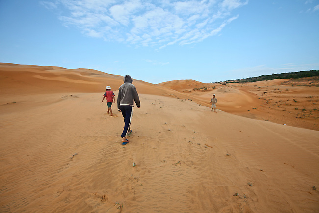 Children walk across the red dunes near Mui Ne, Vietnam. Nov. 11, 2011.