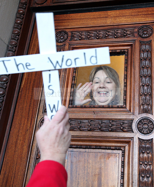 Terry Blanton waves at supporters from inside the capitol building in Frankfort during a support rally for the sit in protest.  Photo by Britney McIntosh | Staff