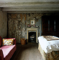Decades worth of paint and paper peels off the walls in this simply furnished guest bedroom