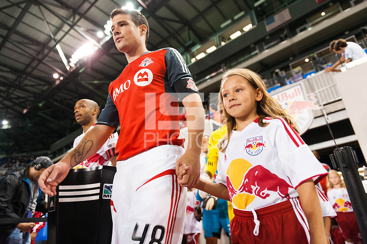 Darren O'Dea (48) of Toronto FC and Thierry Henry (14) of the New York Red Bulls lead their teams onto the field. The New York Red Bulls defeated Toronto FC 4-1 during a Major League Soccer (MLS) match at Red Bull Arena in Harrison, NJ, on September 29, 2012.