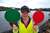 Skim adjudicator Jan XXX who decides on whether a skim is legitimate or not and signals by paddle - at the World Stone Skimming Championships which attracted over 300 entries from all round the world - Easdale is reached by a small open ferry-boat from the Isle of Seil - south of Oban - picture by Donald MacLeod - 25.9.11 - clanmacleod@btinternet.com 07702 319 738 donald-macleod.com