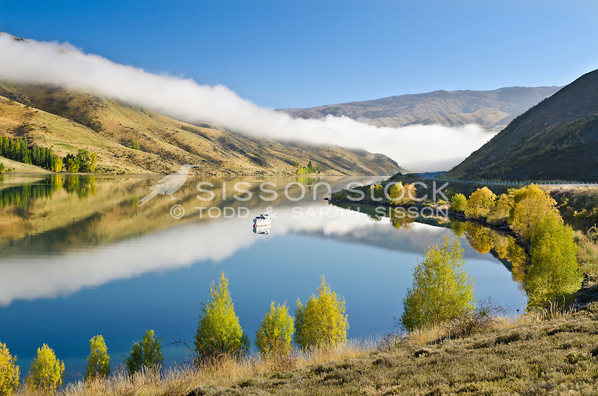 Rolling cloud, white pleasure boat, and Autumn trees reflected in Lake Dunstan near the Clyde Dam, Central Otago, South Island, New Zealand.