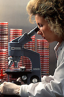 Lab technician at a microscope.